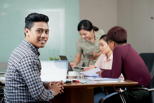 Młody azjatycki mężczyzna obsiadanie przy spotkanie stołem przy pracą
