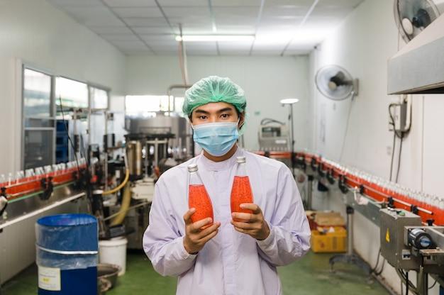 Młody azjatycki mężczyzna pracownik w sterylnym mundurze pokazujący produkt butelkowanego czerwonego soku na linii produkcyjnej w fabryce przetwórstwa napojów