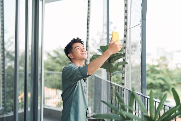 Młody azjatycki mężczyzna robi selfie na balkonie