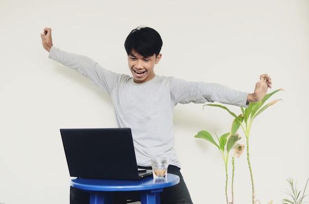 Młody azjatycki mężczyzna siedzący przy laptopie z zadowolonym wyrazem twarzy