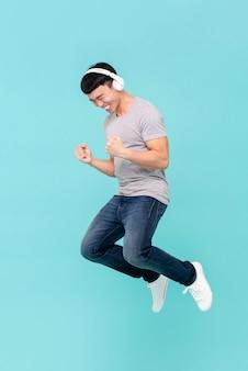 Młody azjatycki mężczyzna skacze szczęśliwie słuchać muzyka