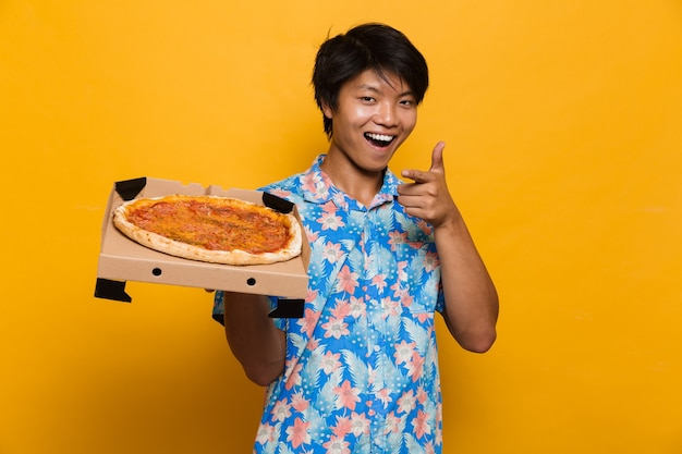 Młody azjatycki mężczyzna stojący na białym tle nad żółtą przestrzenią trzymając wskazując pizzę