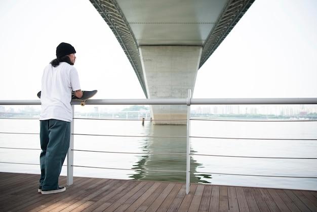 Młody azjatycki mężczyzna trzyma swoją deskorolkę