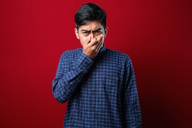 Młody azjatycki mężczyzna ubrany na co dzień w koszulę na czerwonym tle, pachnący czymś śmierdzącym i obrzydliwym, nieznośnym zapachem, wstrzymujący oddech palcami na nosie. nieprzyjemny zapach