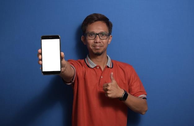 Młody azjatycki mężczyzna ubrany na co dzień w t-shirt z kciukami do góry pokazującym pusty biały ekran smartfona
