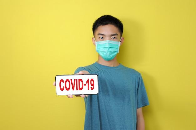 Młody azjatycki mężczyzna ubrany w maskę ochronną pokazujący tekst covid-19 na ekranie telefonu, na białym tle na żółtym tle