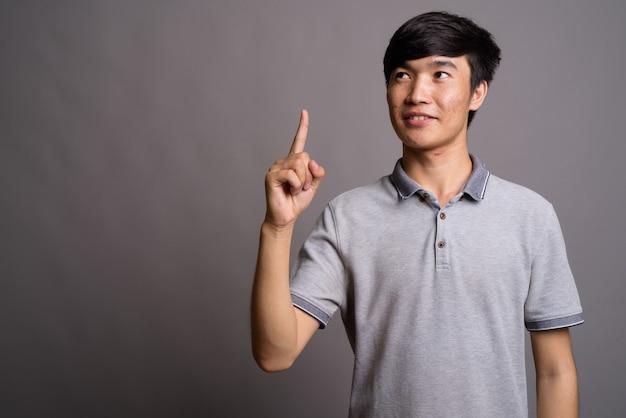 Młody azjatycki mężczyzna ubrany w szarą koszulkę polo na szarej ścianie