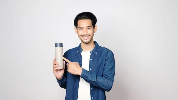 Młody azjatycki mężczyzna uśmiecha się i trzyma butelkę wielokrotnego użytku, patrząc na kamery, stojąc na na białym tle szarym tle