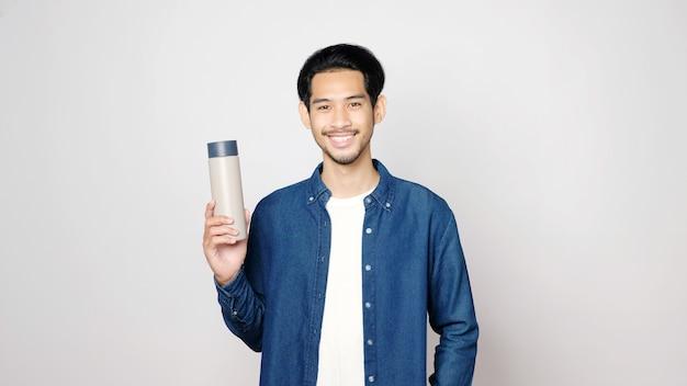 Młody azjatycki mężczyzna uśmiecha się i trzyma butelkę wielokrotnego użytku