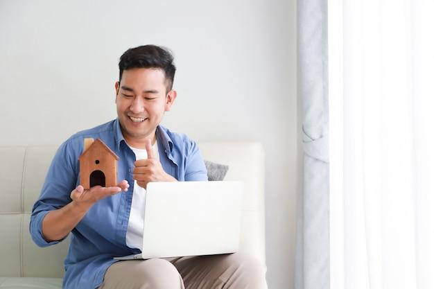 Młody azjatycki mężczyzna w błękitnej koszula z laptopem i małego domu wzorcowym pokazuje dla pożyczki bankowej dla domowego pojęcia w żywym pokoju