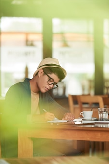 Młody azjatycki modniś siedzi w kawiarni i pisze w notatniku