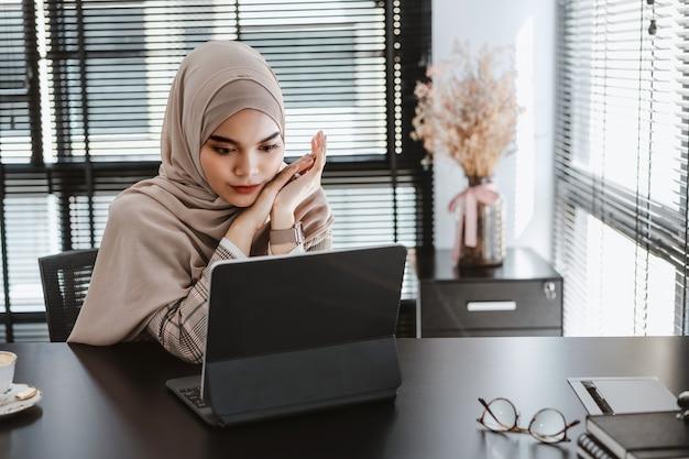 Młody azjatycki muzułmański biznes kobieta brązowy hidżab siedzi i pracuje z laptopem w nowoczesnym biurze.