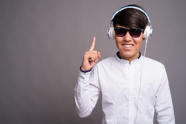 Młody azjatycki nastolatek, słuchanie muzyki na szarym tle