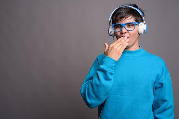 Młody azjatycki nastolatek, słuchanie muzyki przed szarym backgrou