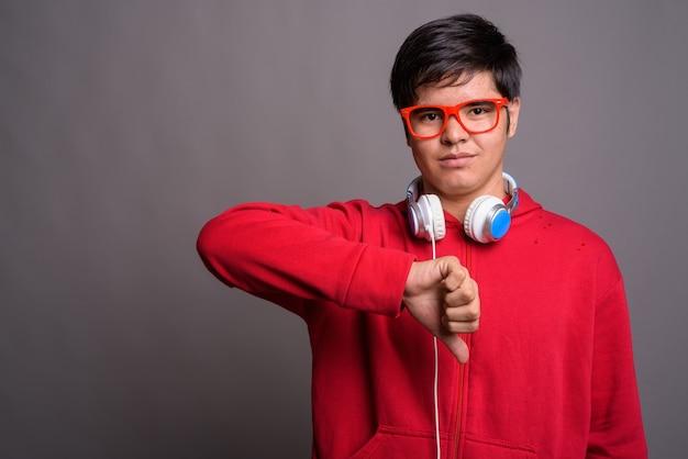 Młody azjatycki nastoletni chłopak sobie słuchawki na szarej ścianie