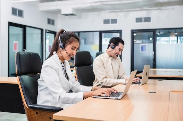 Młody azjatycki operator kobieta agent ze słuchawkami działającą obsługą klienta w call center