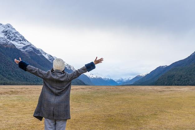 Młody azjatycki podróżnik świętujący sukces w eglinton valley, te anua, south island w nowej zelandii