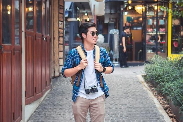 Młody azjatycki podróżny backpacker w ulicznym mieście i chodzący patrzeć popierać kogoś, tajlandia