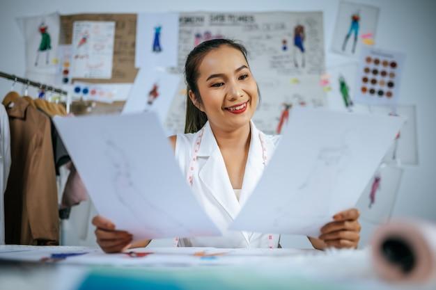 Młody azjatycki projektant mody lub kobieta krawiec sprawdza na ubraniach szkic w ręku