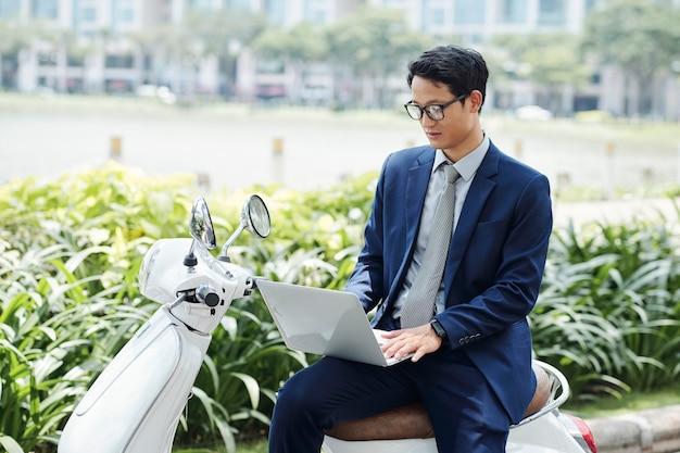 Młody azjatycki przedsiębiorca siedzi na skuterze, pracuje na laptopie i odpowiada na e-maile od kolegów i klientów