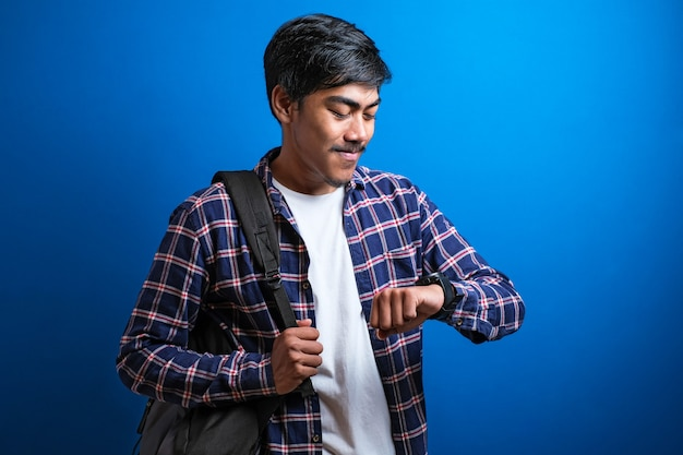 Młody azjatycki student z plecakiem patrzący na zegarek, odizolowany na niebieskim tle