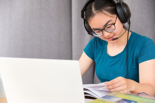 Młody azjatycki studentka nastolatka z okularami zestawu słuchawkowego siedzi na biurku, czytając książkę przy użyciu komputera przenośnego online studium ze szkoły. edukacja z klasy uniwersyteckiej przez wideorozmowę w domu