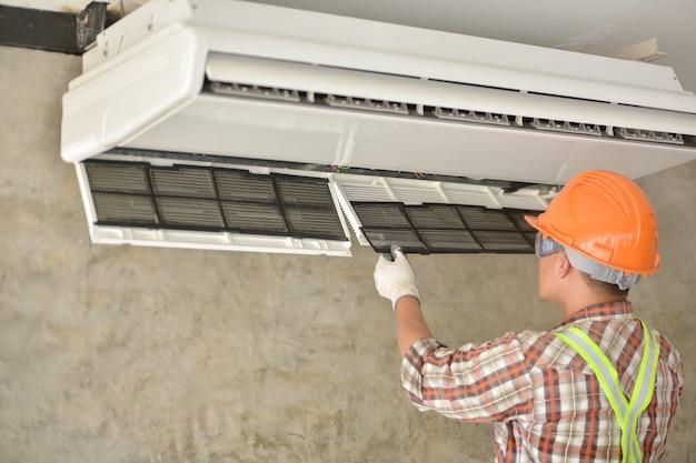 Młody azjatycki technik klimatyzatorów lub technik instalacji klimatyzacji zamierza naprawić klimatyzację w domach i budynkach.