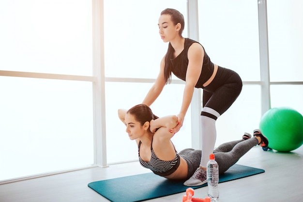 Młody azjatycki trener pomaga europejskiej kobiecie rozciągnąć ciało.