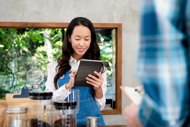 Młody azjatycki żeński personel bierze rozkaz od klienta w sklep z kawą