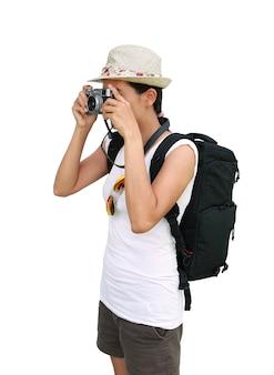 Młody azjatycki żeński podróżnik bierze fotografię z kamerą odizolowywającą na białym tle