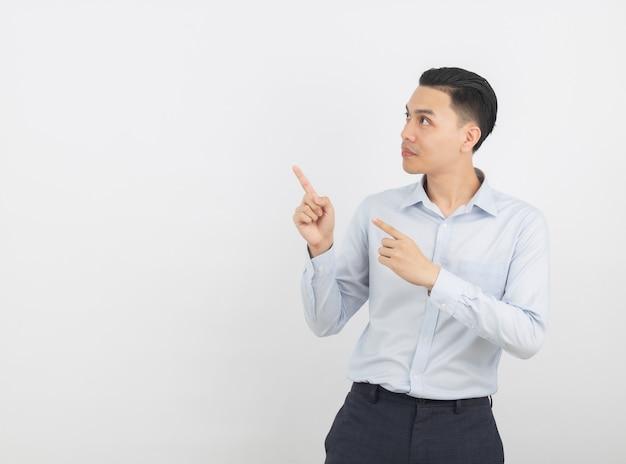 Młody azjatykci biznesowy mężczyzna wskazuje strona z palcem przedstawiać produkt odizolowywającego na bielu z błękitną koszula
