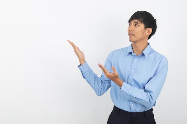Młody azjatykci biznesowy mężczyzna wskazuje strona z rękami z błękitną koszula przedstawiać produkt odizolowywającego na bielu