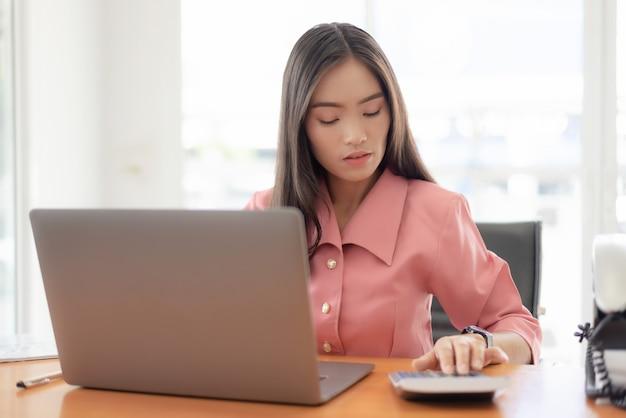 Młody azjatykci bizneswoman sprawdza czas, praca z laptopem.