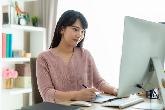 Młody azjatykci bizneswoman używa komputerową pracę od domu
