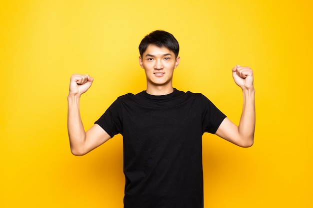 Młody azjatykci chiński mężczyzna świętuje zaskakujący i zadziwiający dla sukcesu z rękami podnosić i otwiera oczy stoi nad odosobnioną kolor żółty ścianą. koncepcja zwycięzcy.