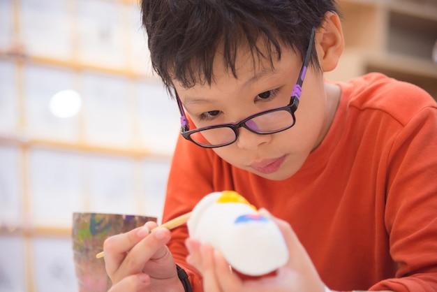 Młody azjatykci chłopiec obrazu rzemiosło kolorem w sala lekcyjnej