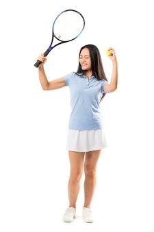 Młody azjatykci gracz w tenisa nad odosobnioną biel ścianą