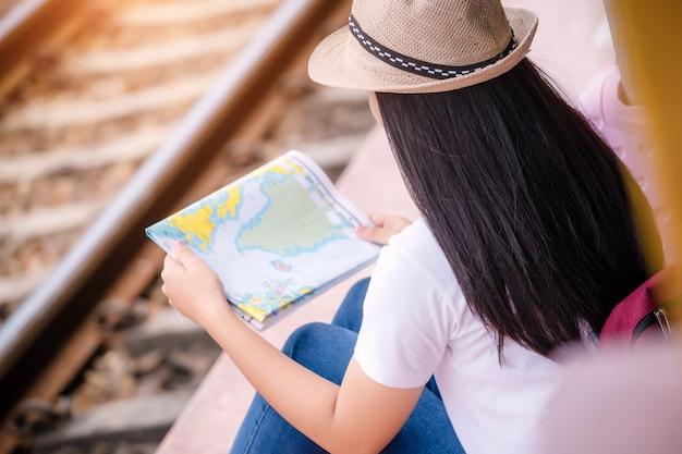 Młody azjatykci gril odprowadzenie przy dworcem przed podróżą. koncepcja pracy i podróży.