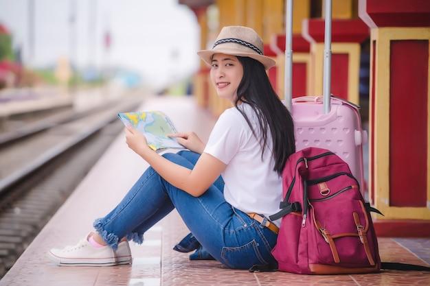 Młody azjatykci gril odprowadzenie przy dworcem przed podróżą.