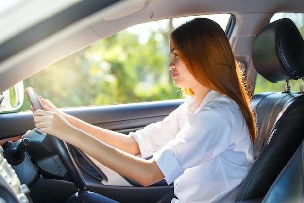 Młody azjatykci kobieta kierowca jedzie samochód na drodze w wsi