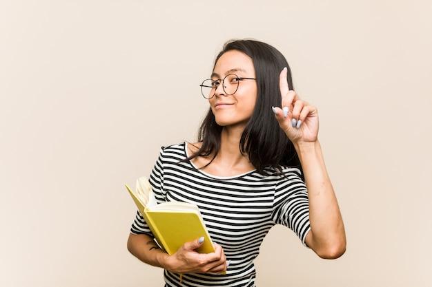 Młody azjatykci kobieta uczeń trzyma książkę ma pomysł, inspiraci pojęcie.