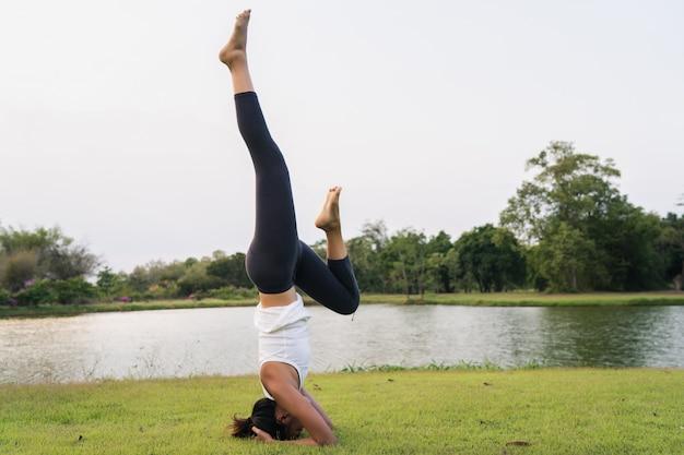 Młody azjatykci kobiety joga outdoors utrzymuje spokój i medytuje podczas gdy ćwiczyć joga