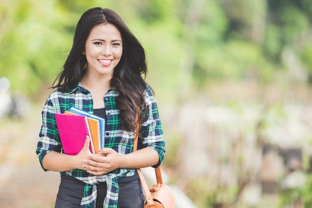 Młody azjatykci kobiety mienie rezerwuje podczas gdy chodzący na parku