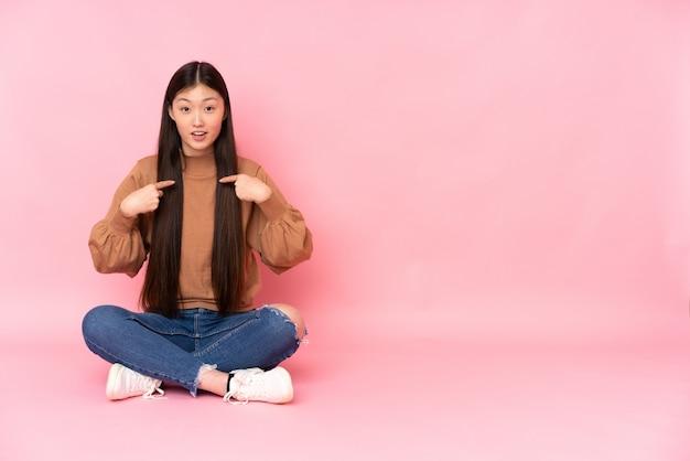 Młody azjatykci kobiety obsiadanie na podłoga na menchii ścianie z zdziwionym wyrazem twarzy