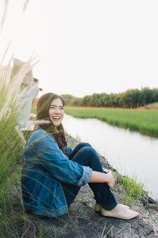 Młody azjatykci kobiety ono uśmiecha się. dziewczyna cieszy się przy piękną naturą z zmierzchem.