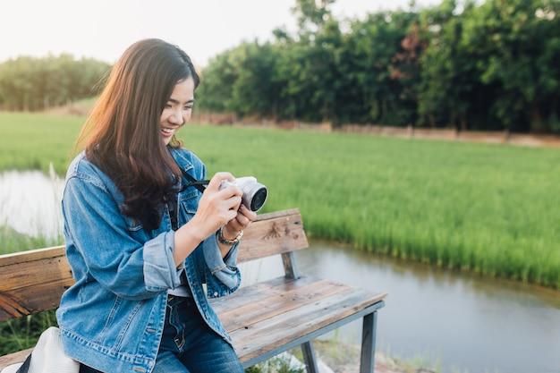 Młody azjatykci kobiety ono uśmiecha się. dziewczyna używa kamerę i cieszy się przy piękną naturą z zmierzchem.