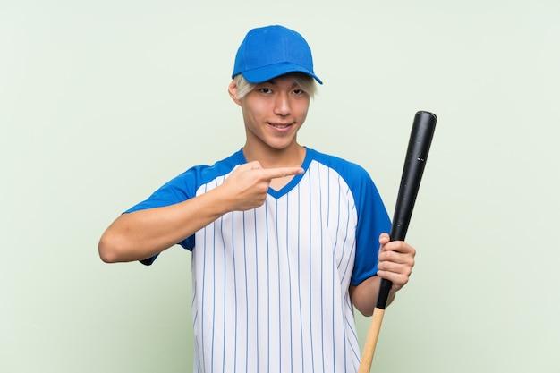 Młody azjatykci mężczyzna bawić się baseballa nad odosobnioną zielenią i wskazuje mnie