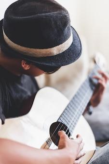Młody azjatykci mężczyzna bawić się hiszpańską gitarę indoors.