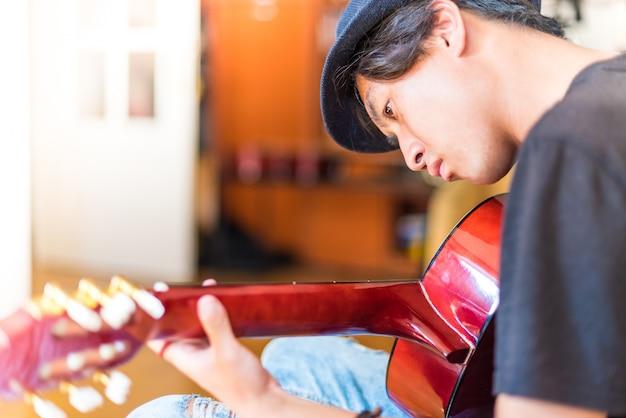 Młody azjatykci mężczyzna bawić się hiszpańską gitarę indoors
