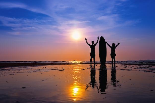 Młody azjatykci mężczyzna bawić się surfboard na plaży przy zmierzchem. relaksująca koncepcja.